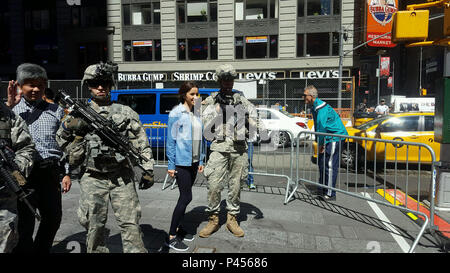 Members of the 1st Battalion 69th Infantry speak with members of the public during an Army Birthday event held on Tuesday, June 14, 2016 in New York's Times Square. The New York Army National Guard infantry battalion supported the Military District of Washington event with equipment and Soldiers in battle gear. ( U.S. Army National Guard photo by Capt. Gavin McDermott/Released) - Stock Photo