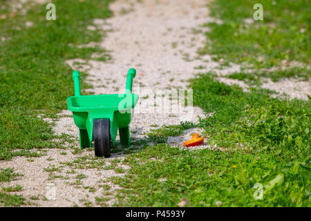 Toy green wheelbarrow with red shovel on grass, abandoned toy, childs play - Stock Photo