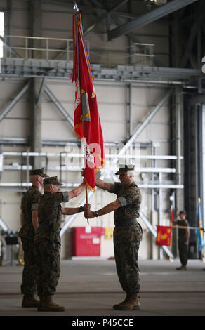 U.S. Marine Corps Sgt. Maj. Jonathan M. Wyble, left, Marine Wing Support Squadron (MWSS) 171 sergeant major, passes the squadron guidon to Lt. Col. James S. Whiteker, outgoing commanding officer of MWSS-171, during a change of command ceremony at Marine Corps Air Station Iwakuni, Japan, June 30, 2016. After serving honorably and faithfully for two years as the squadron commander, Whiteker will be moving onto his next assignment at U.S. Marine Corps Forces South in Miami, Florida, as the logistics officer. (U.S. Marine Corps Photo by Sgt. Jessica Quezada/Released) - Stock Photo