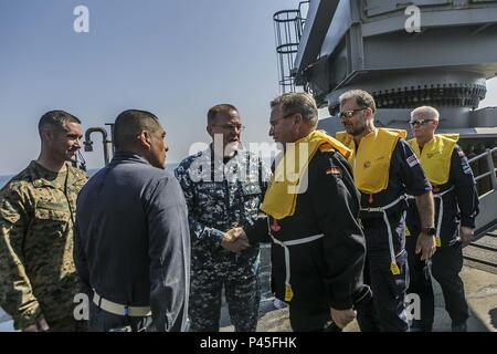 BALTIC SEA (June 04, 2018) Capt. Brian J. Finman, center, deputy commodore of Amphibious Squadron 4, U.S. Marine Corps Maj. Joseph P. Murphy, far left, commander of landing forces for the 26th Marine Expeditionary Unit aboard the Harpers Ferry-class dock landing ship USS Oak Hill (LSD 51), and Cmdr. Rodolfo Jacobo, right, executive officer of the Oak Hill, welcome distinguished visitors aboard the ship during exercise Baltic Operations (BALTOPS) 2018 in the Baltic Sea, June 4, June 4, 2018. BALTOPS is the premier annual maritime-focused exercise in the Baltic region and one of the largest exer - Stock Photo
