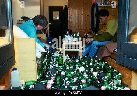A quiet night in - two young men opening a beer bottle each, surrounded by empty bottles - Stock Photo