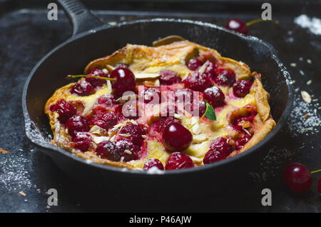 Cherry Dutch Baby, Puff German Pancake on Vintage Pans and Dark Background, Summer Dessert - Stock Photo
