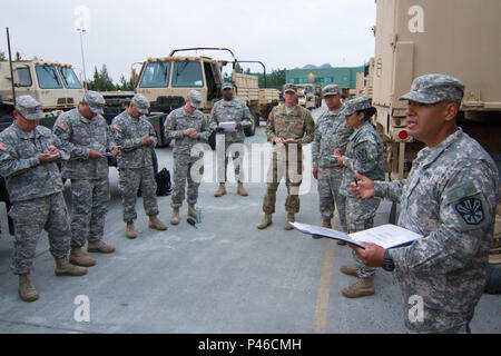 Arizona Army National Guard 2nd Lt. Jonathan Gonzales, support maintenance platoon leader for the 3666th Support Maintenance Company in Phoenix, gives a convoy briefing to Guardsmen from the 3666th, June 28, at Camp Denali on Joint Base Elmendorf–Richardson, Alaska. The Arizona Guardsmen were briefed prior to taking vehicles belonging to the Alaska National Guard to Fort Wainwright, Alaska. (Arizona Army National Guard photo by Staff Sgt. Brian A. Barbour) - Stock Photo