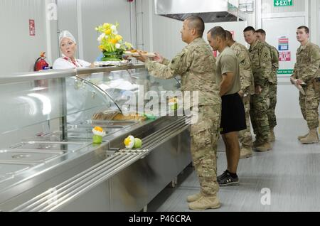Service Members get the first plates of food served at a new dining facility at Life Support Area Danger near Erbil, Iraq, June 30, 2016. The new dining facility will service U.S. and Coalition troops and have a larger and healthier menu than the previous facility. (U.S. Army Photo by Staff Sgt. Peter J. Berardi) - Stock Photo