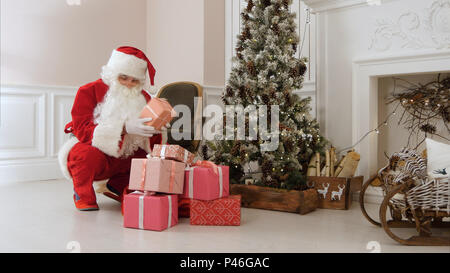 Santa Claus secretly putting gift boxes under the Christmas tree - Stock Photo