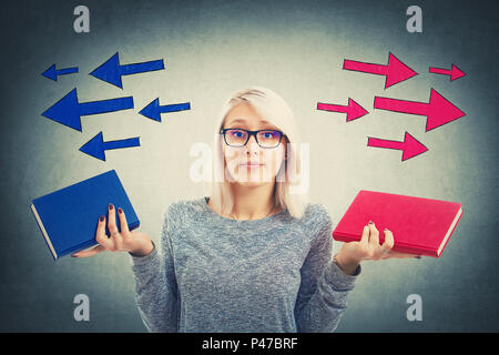 Confused young woman choosing between two books, red and blue, with arrows poinded to the left and right side. Difficult decision, education concept,  - Stock Photo