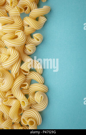 Pasta penne rigate on blue background - Stock Photo