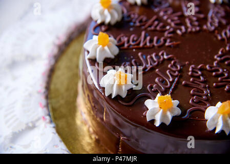 Chocolate cake with white flowers from cream close-up. - Stock Photo