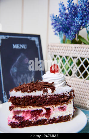 Chocolate cake with cream and cherry on a white plate. - Stock Photo