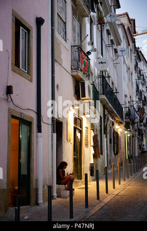 Lisbon, Portugal, woman sits on stairs in Alfama in Lisbon - Stock Photo