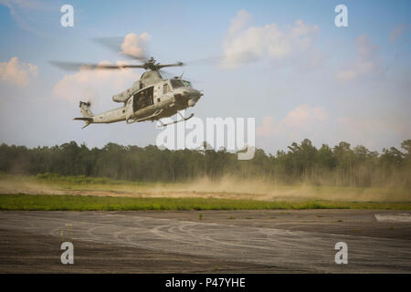 A UH-1Y Venom approaches a landing zone during a training exercise at Camp Davis near Camp Lejeune, N.C., June 17, 2016. The aircraft and its crew are assigned to Marine Light Attack Helicopter Squadron 167, 2nd Marine Aircraft Wing. Familiarization flights familiarize pilots new to the unit with the different landing zones and flight procedures around the Camp Lejeune area. (U.S. Marine Corps photo by Lance Cpl. Aaron K. Fiala/Released.) - Stock Photo