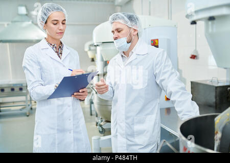 Professional confectioners discussing in factory - Stock Photo
