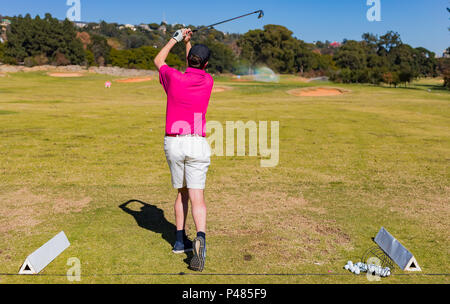 Man teeing off on a golf course Driving Range with a driver - Stock Photo