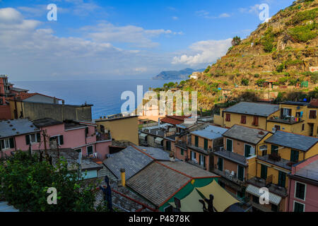 Colorful homes in late afternoon sun and shadows looking out on the sea and sky, Manarola, Cinque Terre - Stock Photo