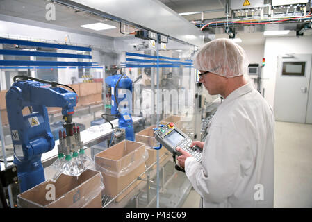 Conveyor belt worker operates a robot that transports insulin bags - modern factory for the production of medicines in the healthcare sector - Stock Photo