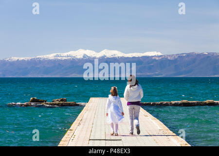 Ohrid, Republic of Macedonia : Children walk on a pier on Ohrid lake with snowcapped mountains in background. - Stock Photo