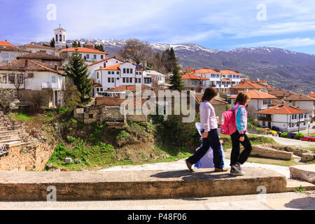 Ohrid, Republic of Macedonia : Children walk past an overview of the old town of Ohrid. - Stock Photo