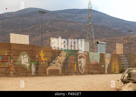 Original US Mexico border fence with prototypes of the proposed new Trump wall erected just beyond, near the Otay Mesa Port of entry in California, US - Stock Photo