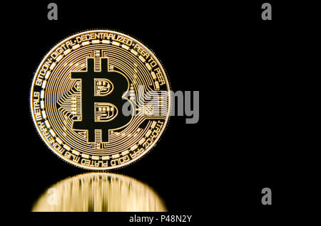 Bitcoin on black background with reflection - Stock Photo