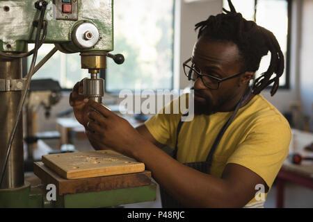 Carpenter adjusting drilling machine - Stock Photo
