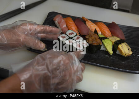 Chef arranging sushi in a tray - Stock Photo