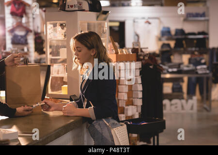 Woman making payment through card - Stock Photo