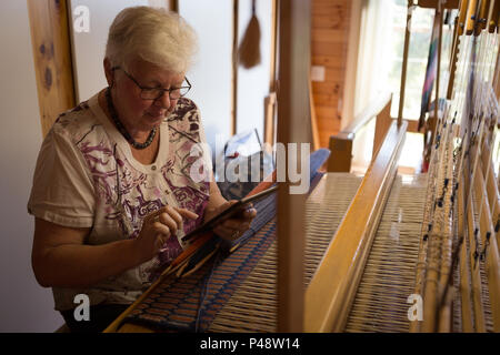Senior woman using digital tablet at shop - Stock Photo