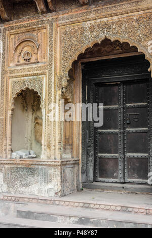 Detail of an exhibit of a gateway to a haveli or mansion typical of Rajasthan with a dog in the alcove, National Crafts Museum, New Delhi, India - Stock Photo