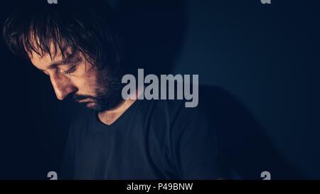 Mental health and depression concept, sad depressed man sulking in dark interior - Stock Photo
