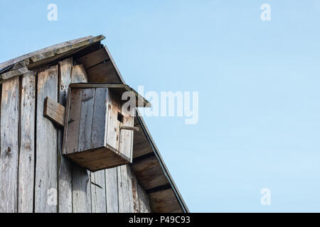 Wooden birdhouse on a  wooden barn wall in a rural area - Stock Photo