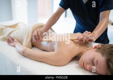 Masseur massaging masseuse at wellness resort - Stock Photo