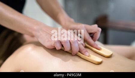 Masseur treating masseuse at wellness saloon - Stock Photo