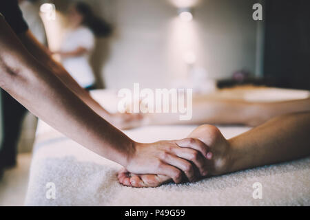 Foot and sole massage in therapeutic relax treatment - Stock Photo