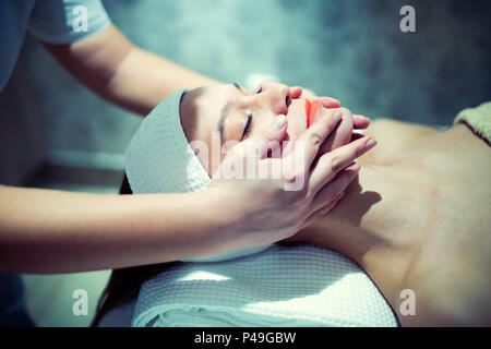 Facial massage treatment by professional at cosmetics saloon - Stock Photo
