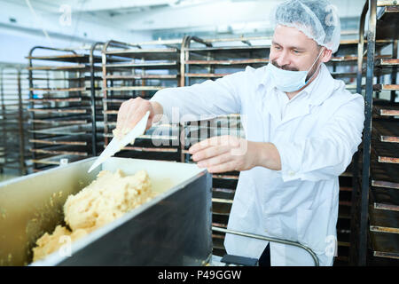 Confectioner mixing dough in factory - Stock Photo