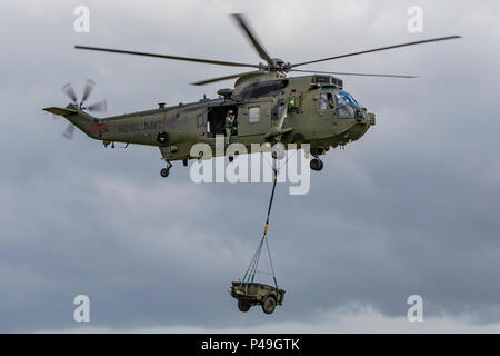 A British Royal Navy Sea King HC4 helicopter carrying out a load lifting demonstration at the Yeovilton Air Day, RNAS Yeovilton, UK on 11/7/15. - Stock Photo