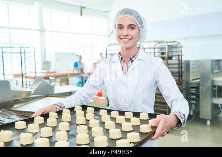 Female baker holding spacing with cakes  - Stock Photo