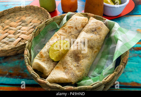 Two shrimp burritos in a basket on a painted table at Baja Fish Taquito restaurant in San Miguel de Allende - Stock Photo