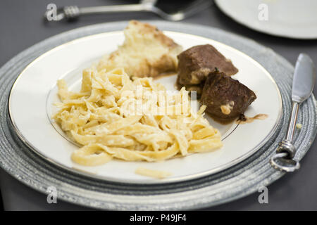 Fettuccine alfredo pasta with sauteed vegetables, chicken marsala, grilled salmon and beef tenderloin medallions - Stock Photo