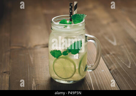 Cold Mojito Cocktail with Ice, Lemon and Mint Leaves in Mason Jar on Rustic Dark Wooden Background as Summer Concept - Stock Photo