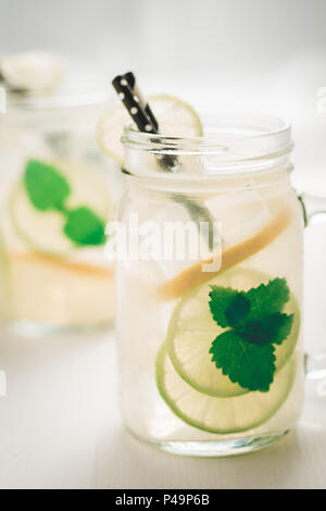 Fresh Mojito Cocktail with Cold Ice, Lemon and Mint Leaves in Mason Jar on White Wooden Background as Bright Summer Concept - Stock Photo