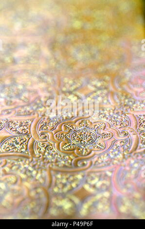 Silver, gold and copper ornamental filigree pattern in metallic vivid color with blurred background and selective focus. Copy space. - Stock Photo