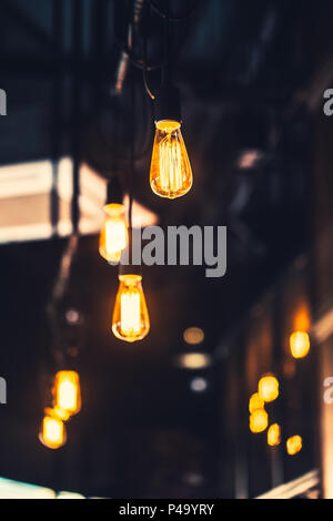 old light bulb cafe decoration. interior lighting vintage retro style with film gain and noise texture. - Stock Photo