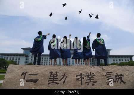Nanjing, China's Jiangsu Province. 21st June, 2018. Graduating master's students toss their academic caps into the sky as they pose for photos at Nanjing Agricultural University in Nanjing, east China's Jiangsu Province, June 21, 2018. Credit: Ji Chunpeng/Xinhua/Alamy Live News - Stock Photo