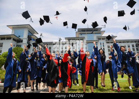 Nanjing, China's Jiangsu Province. 21st June, 2018. Graduating doctorate and master's students toss their academic caps into the sky as they pose for photos at Nanjing Agricultural University in Nanjing, east China's Jiangsu Province, June 21, 2018. Credit: Ji Chunpeng/Xinhua/Alamy Live News - Stock Photo