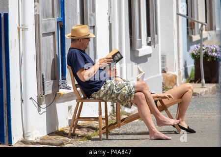 Rame Peninsula, Cornwall, UK Weather. As a high pressure moves in across many southern parts of the UK period of good weather with warm to hot sunshine is on the way.  A couple relaxing in the hot sunshine at the seafront at the coastal seaside village of Kingsand, Cornwall - Stock Photo