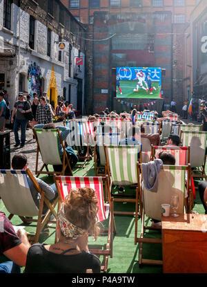 London, UK. 21st June 2018. Fans watching the France v Peru match in deckchairs in Camden Market London UK Credit: Martyn Goddard/Alamy Live News - Stock Photo
