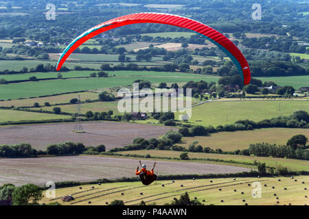Devil's Dyke, UK. 21st June 2018. Paragliders taking advantage of the fantastic late afternoon weather conditions at Devil's Dyke, near Brighton, and take to the skies over the Sussex Weald Credit: Andrew Hasson/Alamy Live News - Stock Photo