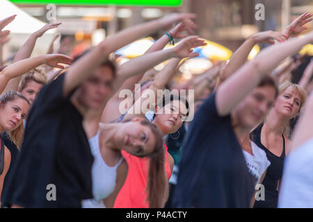 Thousands of yoga practitioners pack Times Square in New York to practice yoga on the first day of summer, Thursday, June 21, 2018. The 16th annual Solstice in Times Square, 'Mind Over Madness', sponsored by American Eagle Outfitters' athleisure brand Aerie, stretches the yogis' ability to block out the noise and the visual clutter that surround them in the Crossroads of the World. The first day of summer has been declared the International Day of Yoga by the United Nations. (© Richard B. Levine) Credit: Richard Levine/Alamy Live News - Stock Photo