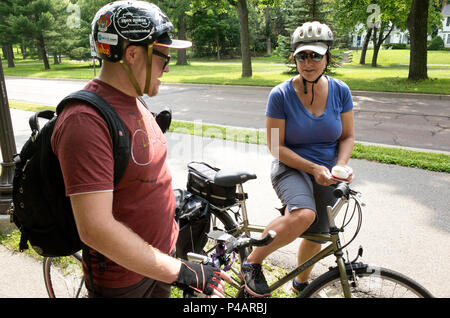 Man and woman in conversation while taking a break on a bicycle trip wearing helmets. Minneapolis Minnesota MN USA - Stock Photo